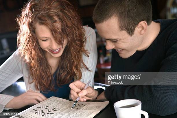 Couple doing crossword puzzle at table