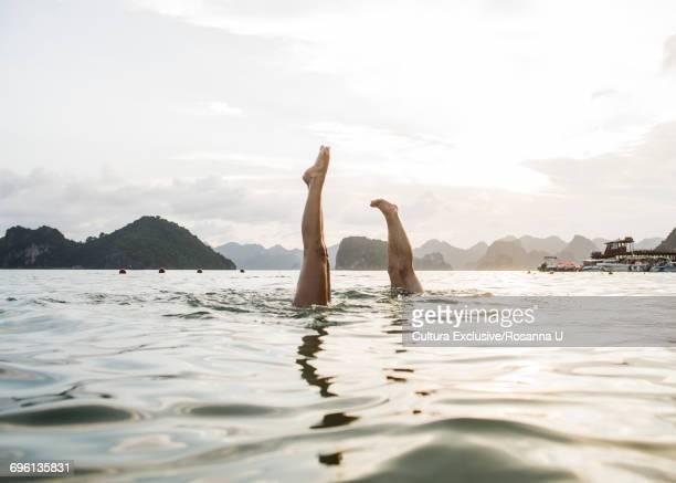 Couple doing handstand in waters of Ha Long Bay, Vietnam