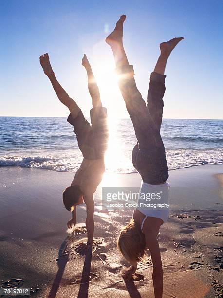 Couple doing handstand on a beach