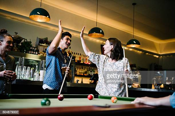 Couple doing high five by pool table in bar