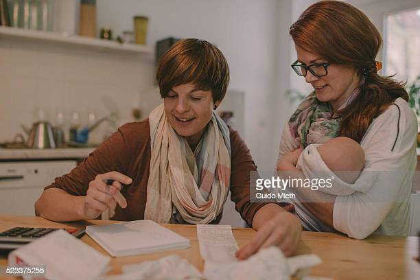 couple doing household  budget. - lgbtq  and female domestic life stock pictures, royalty-free photos & images