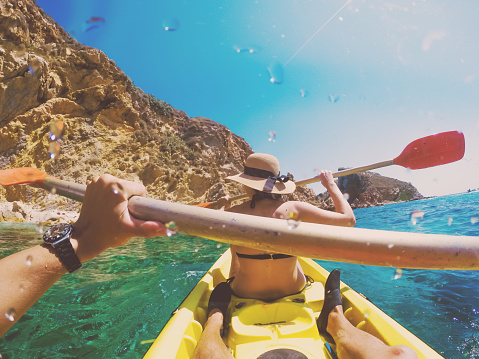 Couple doing kayak taking picture from boyfriend personal perspective exploring the natural Medes islands in the shoreline of Costa Brava Mediterranean Sea during summer vacations in a paradise place. - gettyimageskorea