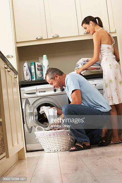 Couple doing laundry, man loading washing machine, low angle view