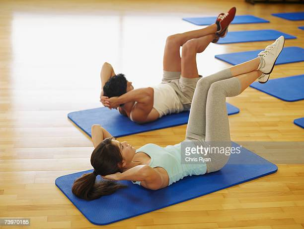 Couple doing mat exercises in a fitness studio