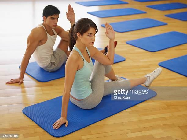 Pareja haciendo ejercicios de gimnasio con una estera de estudio