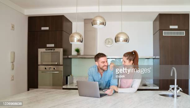 couple doing online shopping at home - izusek stock pictures, royalty-free photos & images