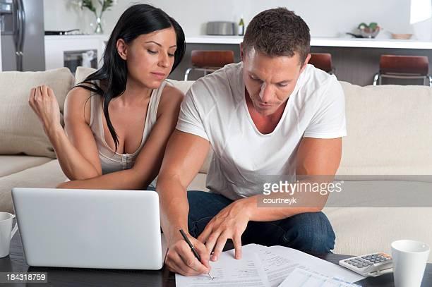 casal fazendo documentação com um laptop - preencher um formulário - fotografias e filmes do acervo
