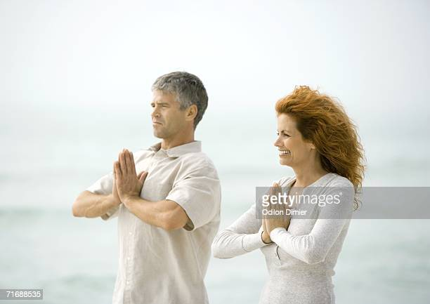 Couple doing relaxation exercises together on beach