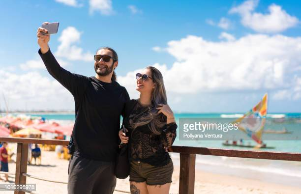 couple doing selfie on the beach - porto galinhas stock photos and pictures
