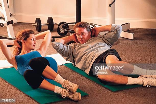 Couple doing sit-ups on floor mats