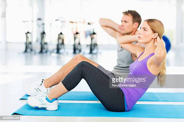Couple Doing Sit-Ups Together In Health Club