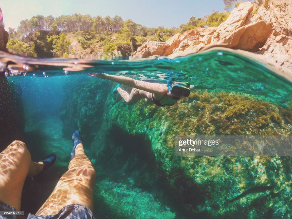 Couple doing snorkel exploring the natural cave in the shoreline of Costa Brava Mediterranean Sea during summer vacations in a paradise place taking picture with dome cover and underwater view. : Stock Photo
