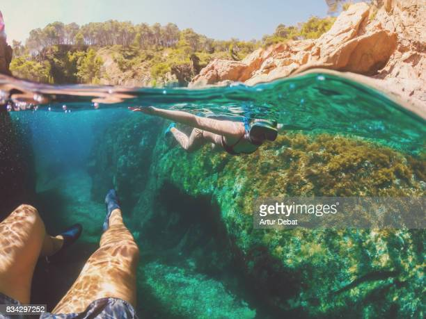 Couple doing snorkel exploring the natural cave in the shoreline of Costa Brava Mediterranean Sea during summer vacations in a paradise place taking picture with dome cover and underwater view.