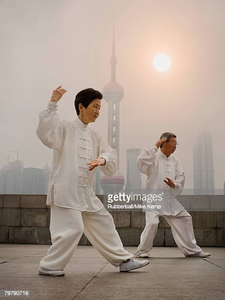Couple doing tai chi outdoors with city skyline in background