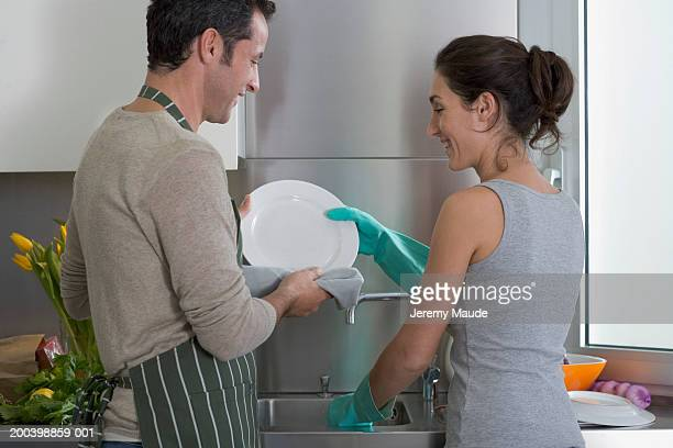 Couple doing washing up, rear view
