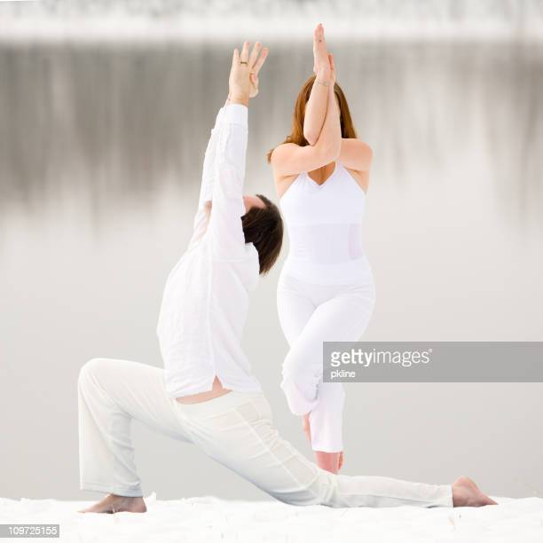 Couple Doing Yoga Poses in the Snow