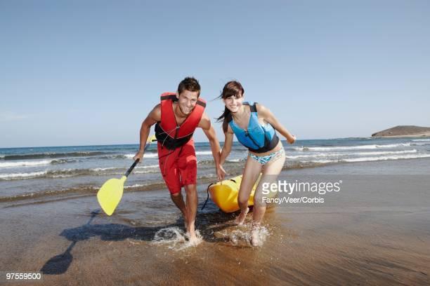 Couple Dragging a Sea Kayak
