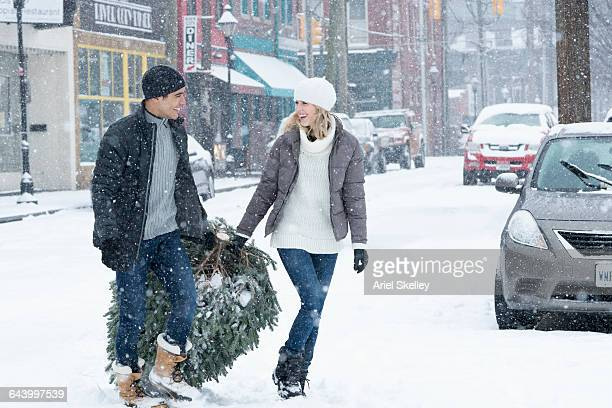 Couple dragging Christmas tree in snow