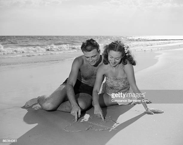 Couple drawing heart in sand at beach