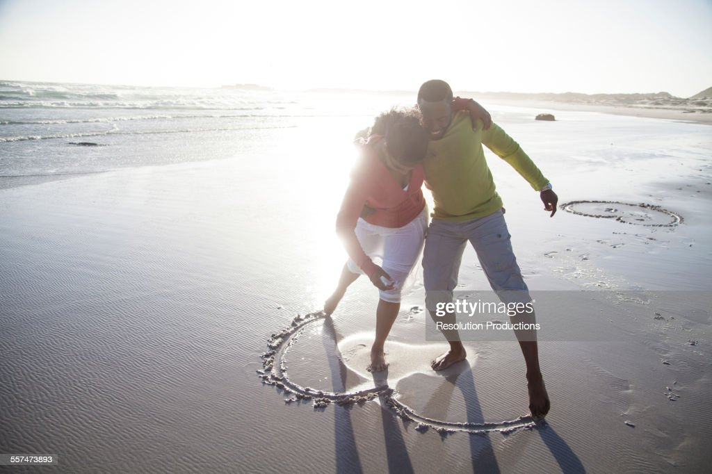Couple drawing heart in sand on beach : Stock Photo