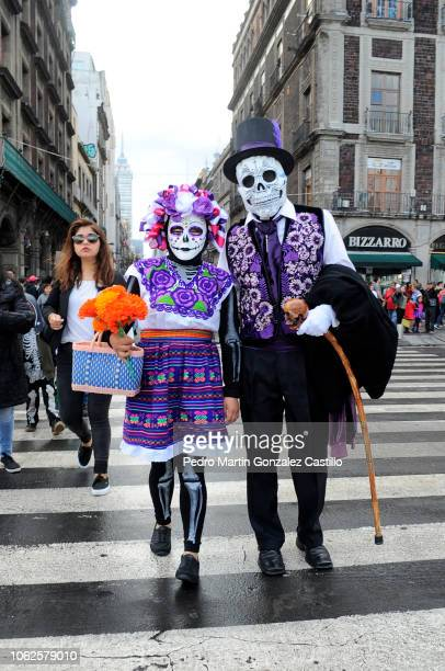 A couple dressed as a skeleton walk by the Francisco I Madero Avenue as part of the Day of the Dead celebrations on November 1 2018 in Mexico City...