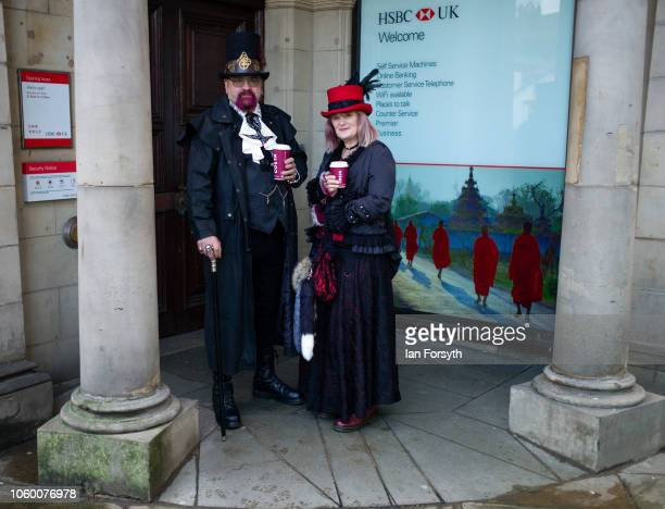 Couple dressed as goths shelter from the wind during Whitby Goth Weekend on October 27, 2018 in Whitby, England. The Whitby Goth weekend began in...