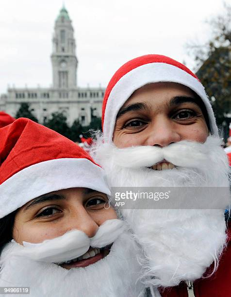 A couple dressed as Santa Claus pose for a picture as they take part in a parade in downtown Porto December 20 2009 Thousands marched in an attempt...
