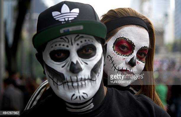 A couple dressed as The Catrina and The Catrin pose for pictures at the Angel of Independence square before taking part in the Procession of the...