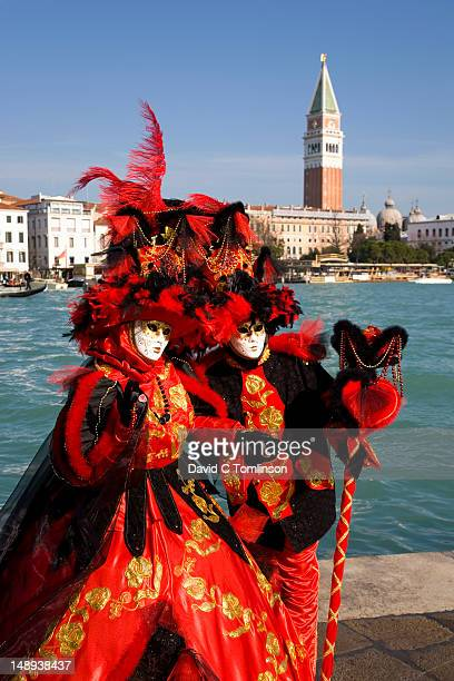 Couple dressed in carnival costumes and masks posing in front of the Campanile di San Marco during the Venice Carnival, Punta della Dogana, Dorsoduro district.