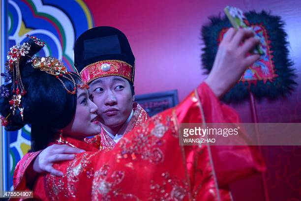 A couple dressed in Chinese traditional wedding dress take a photo at a wedding expo in Beijing on February 28 2014 Unlike in the west Chinese...