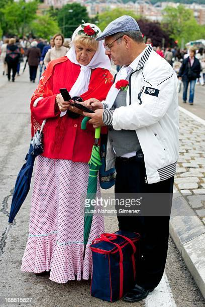A couple dressed in chulapo traditional clothing of the San Isidro looks on during the festivities on May 15 2013 in Madrid Spain