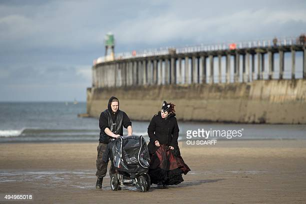 A couple dressed in costume wheel a pushchair along the beach during the biannual Whitby Goth Weekend festival in Whitby northern England on October...