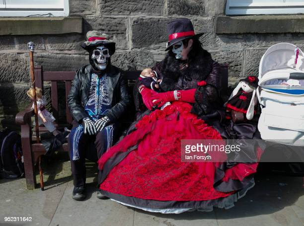 A couple dressed in Goth clothing carrying baby dolls sit on a bench during Whitby Gothic Weekend on April 28 2018 in Whitby England The Whitby Goth...