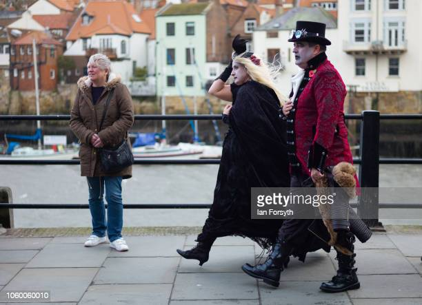 A couple dressed in goth clothing walk along the harbour during Whitby goth Weekend on October 27 2018 in Whitby England The Whitby goth weekend...