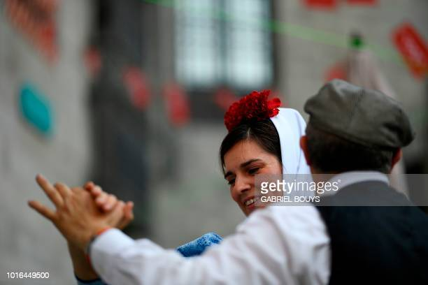 A couple dressed in Madrid's traditional attire Chulapos dance during the Feast of La Paloma Virgin in Madrid on August 13 2018 Madrid's history and...