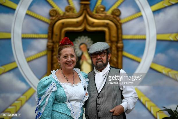 A couple dressed in Madrid's traditional attire Chulapos pose during the Feast of La Paloma Virgin in Madrid on August 13 2018 Madrid's history and...