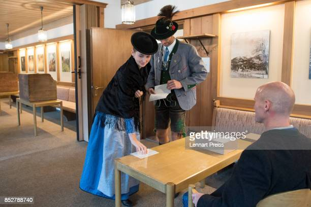 A couple dressed in traditional Bavarian clothes collect their election ballots as they arrive at a polling station during German federal elections...