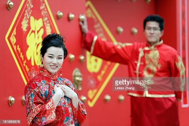 A couple dressed in traditional Chinese costumes have wedding portraits made on Valentine's Day February 14 2013 in Beijing China Young Chinese...