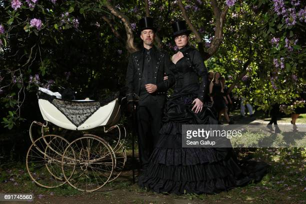 A couple dressed in Victorianinspired outfits and wheeling a baby pram attend the Victorian Picnic on the first day of the annual WaveGotikTreffen...