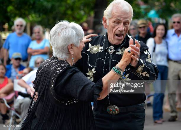 Couple dressed in western clothing and accessories dance to live music on the historic Plaza in Santa Fe, New Mexico.