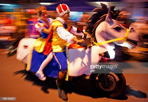 A couple dressed participates in the MotoHalloween party 2012 on November 1 in Cali Valle del Cauca department Colombia AFP PHOTO/Luis ROBAYO
