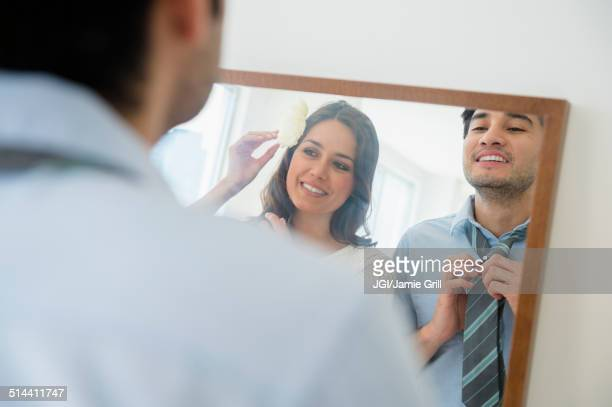 Couple dressing in front of mirror