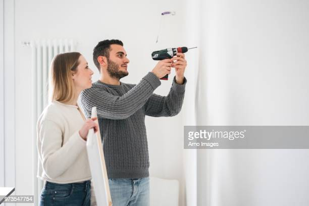 couple drilling wall to hang picture - drill stock pictures, royalty-free photos & images