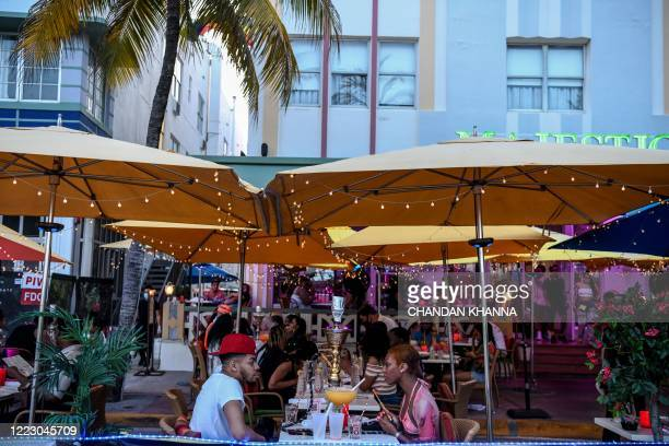 Couple drink at a restaurant on Ocean Drive in Miami Beach, Florida on June 26, 2020. - They are itching for a good time after months of lockdown,...