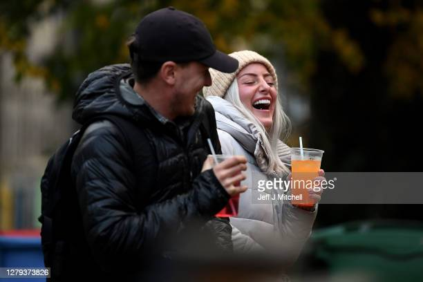 Couple drink from takeaway glasses outside a pub in the Grassmarket following last orders at 6pm on October 9, 2020 in Edinburgh, Scotland. Pubs and...