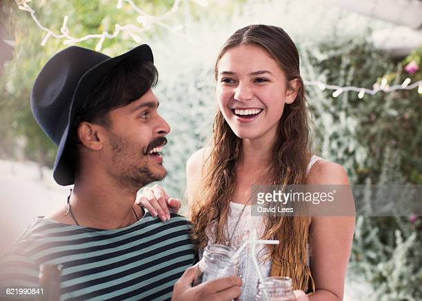 Couple drinking and relaxing at poolside party