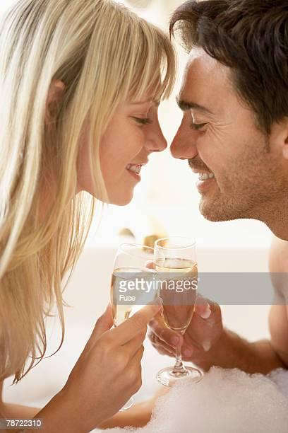 couple drinking champagne in bubble bath - couple and kiss and bathroom stock photos and pictures