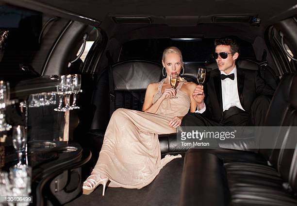 couple drinking champagne in limo - evening gown stock photos and pictures