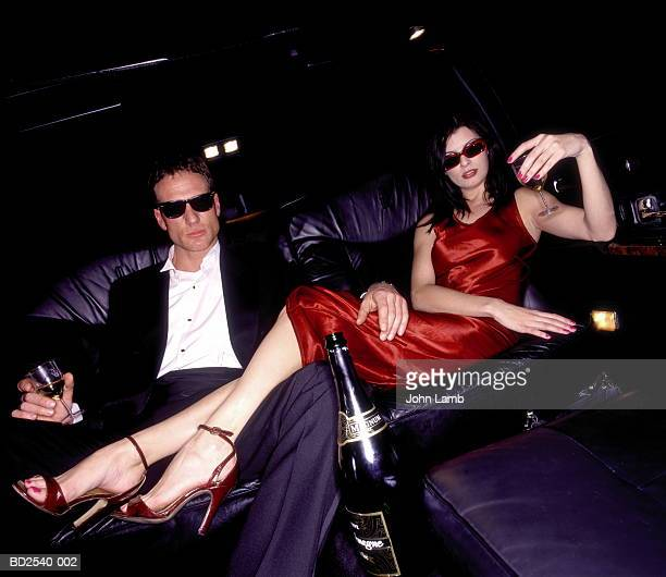 couple drinking champagne on back seat of limousine - millionnaire stock photos and pictures