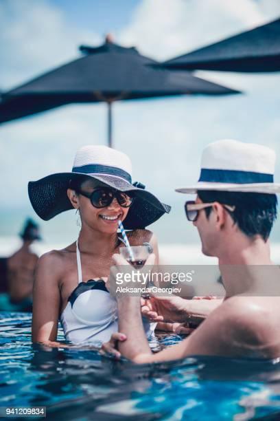 Paar drinken Cocktail flirten en genieten van de zonsondergang in Infinity zwembad
